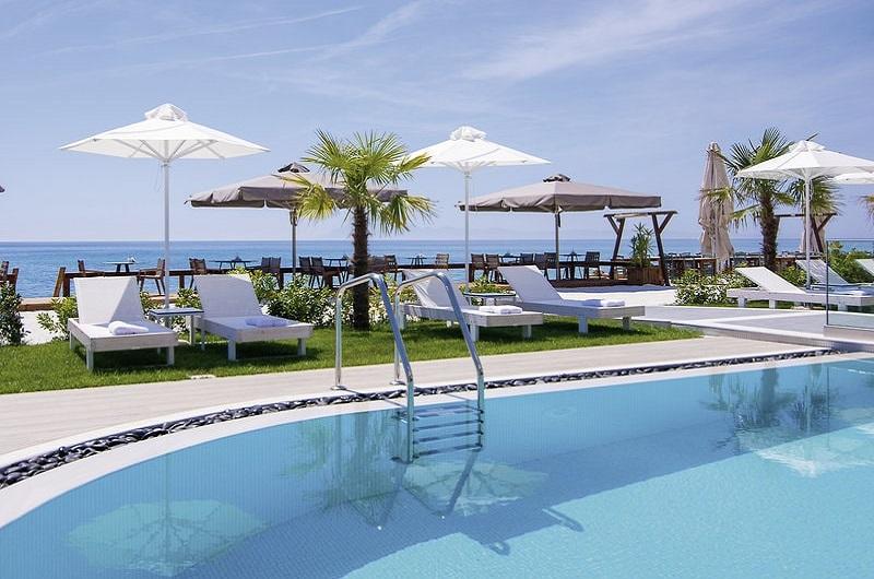 Aegean Infinity Deluxe Hotel Limenaria Thassos Bilder Außenbereich mit Pool Sonnenschirmen und Sonnenliegen-min